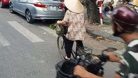 Vietnam Bike Woman 2.mp4. Scene from Hanoi Vietnam Asia Slow Tracking Motion shot of Vietnamese Woman riding traditional bike wearing stock footage