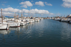 Scene in the harbor with boats and yachts against a blue sky Stock Photography
