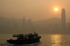 Scene - Hong Kong. Boat sailing towards Hong Kong island at sunset Royalty Free Stock Images