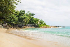 Scene of idyllic beach and forest with an old bridge Stock Images