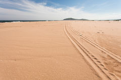 Scene of a long car trace on the beach on sunny day. Wide angle. Royalty Free Stock Image