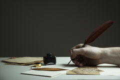 Scene with a man`s hand writing a letter or story with vintage q. Uill and old pieces of paper on white table - with copy space for text Royalty Free Stock Photos
