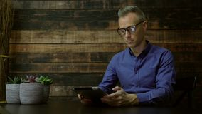 Modern man using a tablet in a cafe. Scene of a modern man using a tablet in a cafe stock video footage