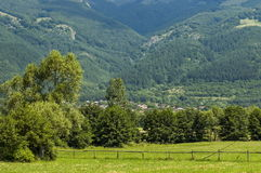 Scene with mountain glade, forest and residential district of bulgarian village Anton, Central Balkan mountain, Stara Planina Royalty Free Stock Image