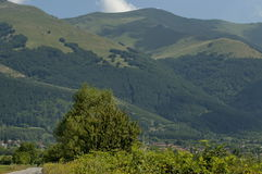 Scene with mountain glade, forest and residential district of bulgarian village Anton, Central Balkan mountain, Stara Planina Royalty Free Stock Photo