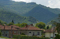 Scene with mountain glade, forest and residential district of bulgarian village Dushantsi, Central Balkan mountain, Stara Planina Royalty Free Stock Photo