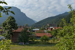 Scene with mountain top, forest, glade and residential district of bulgarian village Beli Iskar, Rila mountain Stock Photo