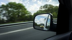 Reflection of a car mirror that shows a bus that drives fast. Scene from a moving motorway on a highway royalty free stock photos