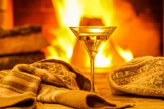 Scene near cozy fireplace with a glass of martini. Glass of martini wine against cozy fireplace background, winter vacation, winter vacation, in country house Royalty Free Stock Images