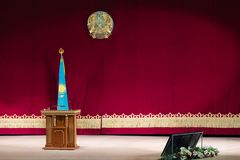 Scene for an official or president. Concept Kazakh news. The coat of arms, the flag of the Republic of Kazakhstan and the podium stock photography
