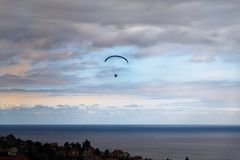 Scene of Paraglider over the sea against cloudy sky. Scene of Paraglider over the sea coastline against cloudy blue sky at sunset. Portuguese island of Madeira stock photography