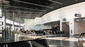 A scene with people sitting on benches in Vienna International Airport, Austria stock image