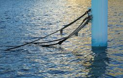 Pillar for the mooring of the port. Scene of the pillar for the mooring of the port of the setting sun reflecting in sea level Stock Images