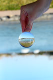 Scene reflection beyond glass sphere Stock Photo