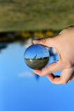 Scene reflection beyond glass sphere. Close up Royalty Free Stock Photo