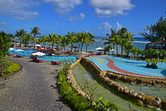 Scene of a Resort Swimming Pool Area at West Coast of Mauritius Island. Tourism in Mauritius is an important component of the Mauritian economy as well as a Royalty Free Stock Photos