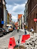 Road works on narrow street in old part of the Torun city in Polandcity. Scene of road works on street. Women weared reflecting vest redirect traffic. Two men Royalty Free Stock Photography