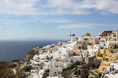 Scene in Santorini in Greece. Scene with white and blue house and buildings, windmill, and church in Santorini island in Greece in May. blue sky and white cloud Stock Images
