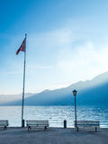 Scene side of Lake Maggiore in Switzerland. Outdoor scene view side of Lake Maggiore with bench and flag in Locarno, Switzerland Royalty Free Stock Photography