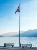 Scene side of Lake Maggiore in Switzerland. Outdoor scene view side of Lake Maggiore with bench and flag in Locarno, Switzerland Stock Photography