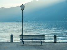 Scene side of Lake Maggiore in Switzerland. Outdoor scene view side of Lake Maggiore with bench and light pole in Locarno, Switzerland Royalty Free Stock Image