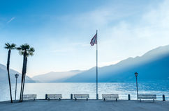 Scene side of Lake Maggiore in Switzerland. Outdoor scene view side of Lake Maggiore with bench, palm tree and flag in Locarno, Switzerland Royalty Free Stock Image