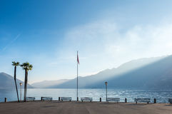 Scene side of Lake Maggiore in Switzerland. Outdoor scene view side of Lake Maggiore with bench, palm tree and flag in Locarno, Switzerland Stock Photos