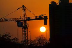 Silhouette dusk construction site of crane over sunset background Royalty Free Stock Photos