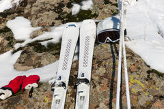 Scene of ski equipment on rocks and snow Royalty Free Stock Images