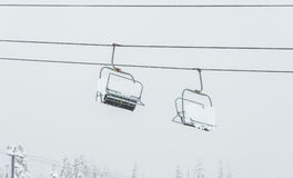 Scene of ski lift with seats  over the mountain. Stock Images