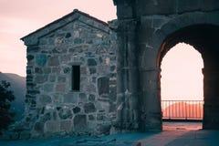 The scene of sunset through the arch in Jvari Church near Mtskheta, Georgia. The scene of sunset landscape through the arch in Jvari Church near Mtskheta Royalty Free Stock Photos