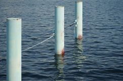 Pillar for the mooring of the ship which appeared on the sea surface. Scene of three pillars for the mooring of the ship which appeared on the sea surface royalty free stock image