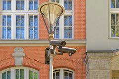 Three security cameras on street lamp royalty free stock image