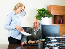 Scene of two aged and smiling co-workers Stock Image