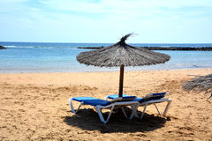 Scene with two deck chairs and umbrella on the beach .Canary Islands.Spain. Stock Photos