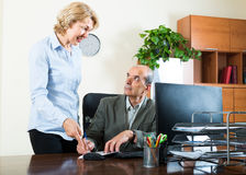 Scene of two mature and smiling co-workers Stock Photos