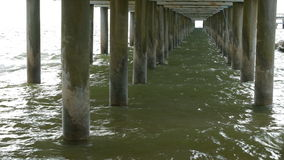 Scene of under the old concrete jetty. With sea shore and sky stock video