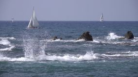 Waves crash against sharp rocks near sail boat. Scene of waves crashing against sharp rocks near a sailboat stock video footage