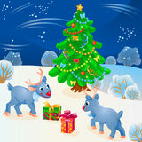 Scene of winter night with Christmas tree, two young reindeers and gift boxes in front of them Stock Photo
