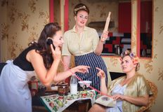 Scene with women fun talking to each other in the kitchen. Retro style, vintage, pin-up. Scene with women who have fun talking to each other in the kitchen stock image