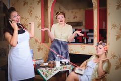 Scene with women fun talking to each other in the kitchen. Retro style, vintage, pin-up. Scene with women who have fun talking to each other in the kitchen royalty free stock photos