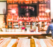 Scene of wooden table top with abstract blurred background in open restuarant. Stock Photos