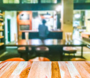 Scene of wooden table top with abstract blurred background in open restuarant. Royalty Free Stock Photos