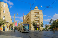 Scene of Yafo Street, Jerusalem. JERUSALEM, ISRAEL - SEPTEMBER 23, 2016: Scene of Yafo Street, with the Generali building, a tram, locals and visitors, in Royalty Free Stock Images