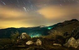 Scenerey hermoso de la noche con las montañas debajo del cielo nublado Foto de archivo