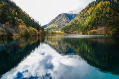 Sceneria jezioro w lesie z Kolorowymi liśćmi i górą w jesieni Fotografia Royalty Free