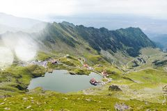 Scenery of Balea Lake and serpentine road in Fagaras Mountain. S, Romania. Cloudy sky. Wide shot stock image