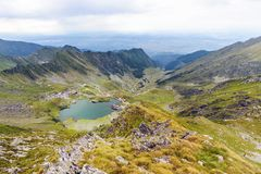 Scenery of Balea Lake and serpentine road in Fagaras Mountain. S, Romania. Cloudy sky. Wide shot royalty free stock images