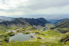 Scenery of Balea Lake and serpentine road in Fagaras Mountains. Romania. Cloudy sky. Wide shot stock photography