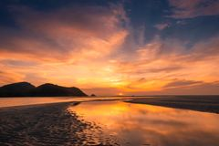 The scenery of the beach in sunset. Scenery of golden beach early morning in sunrise over sea and orange sky above it.Sea south Thailand,Koh Yao Yai,Phang Nga stock photo
